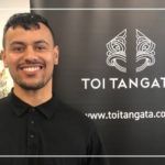 Enoka Wehi wearing a black shirt, standing in front of a black and white Toi Tangata