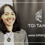 Wanakia Heather-Kingi wearing a white t-shirt, tweed jacket and pounamu necklace, standing in front of a black and white Toi Tangata banner.